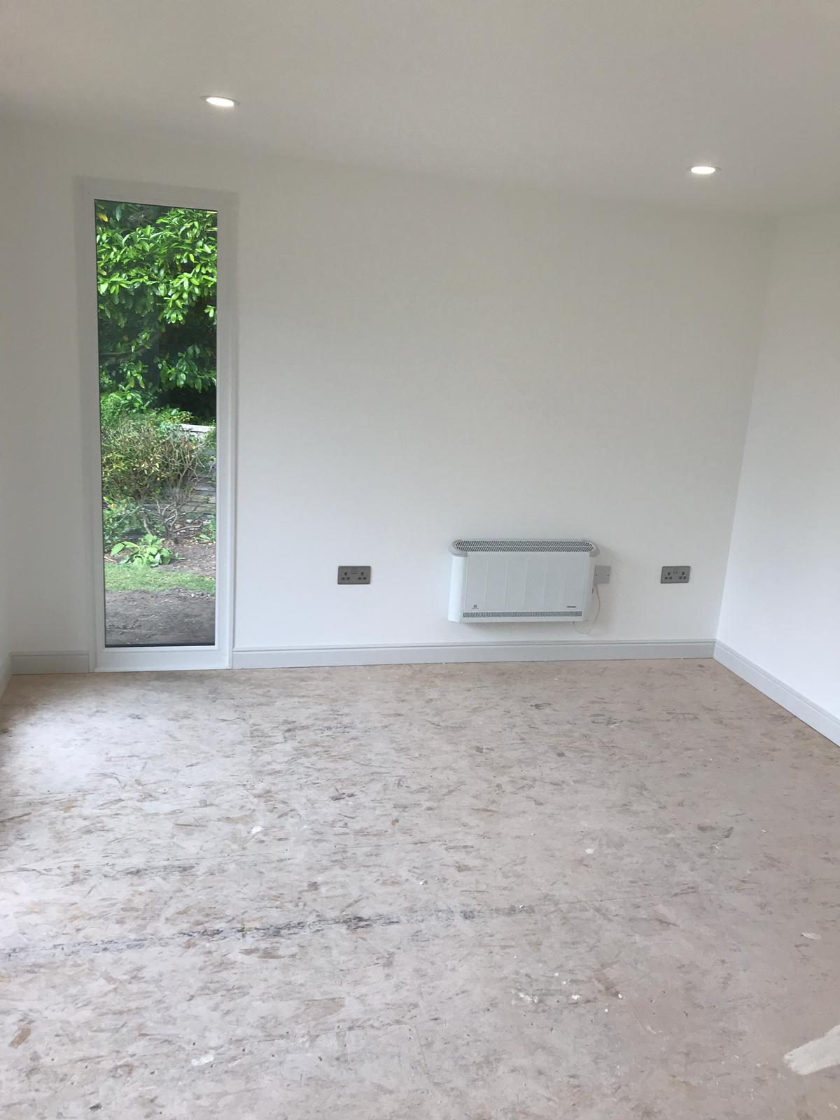 Plastered and painted interior upgrade with inset downlights, slimline heater and full height fixed window.